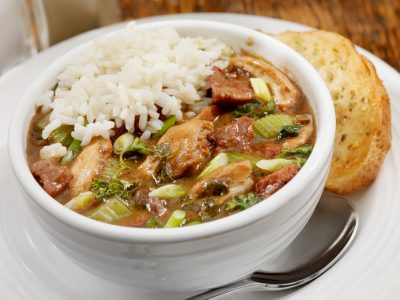 cup of chicken and sausage gumbo with big scoop or rice and piece of bread