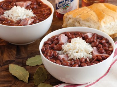 two bowls red beans and rice with ham and French bread and Crystal hot sauce