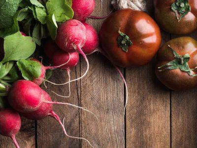 fresh radish and heirloom tomato on wood board