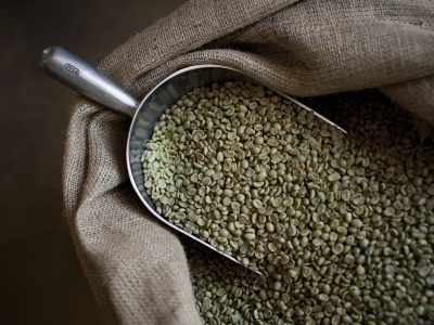 green coffee beans in bag with scoop
