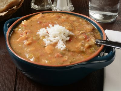 light brown gumbo in bowl with scoop of rice