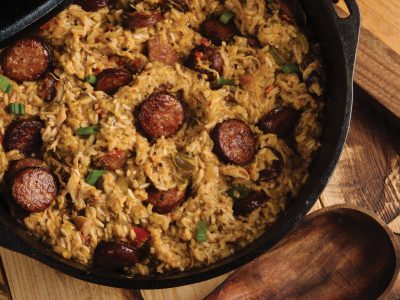 Rouses original sausage jambalaya in cast iron Dutch oven with wooden spoon