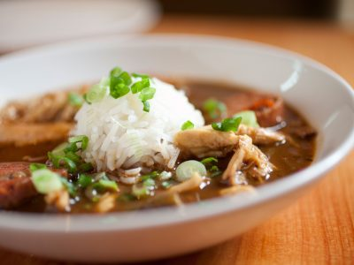 cajun style chicken sausage gumbo with scoop of white rice and green onion tops