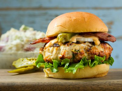 Gumbo burger with sausage and okra and chicken patty on bun, burger issue Rouses Magazine