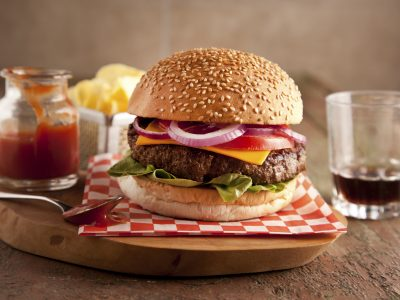Classic Cheeseburger with seeded bun on red and white napkin