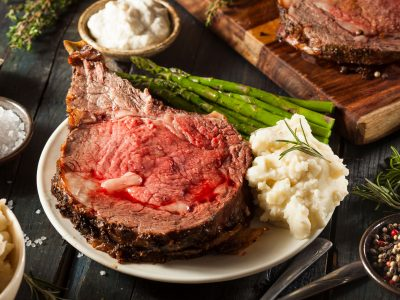 close up plate of prime rib with mashed potatoes and horseradish sauce