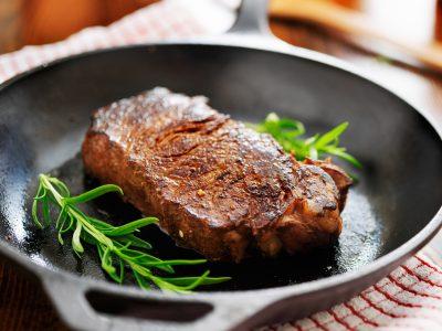 Black iron skillet with New York Strip steak